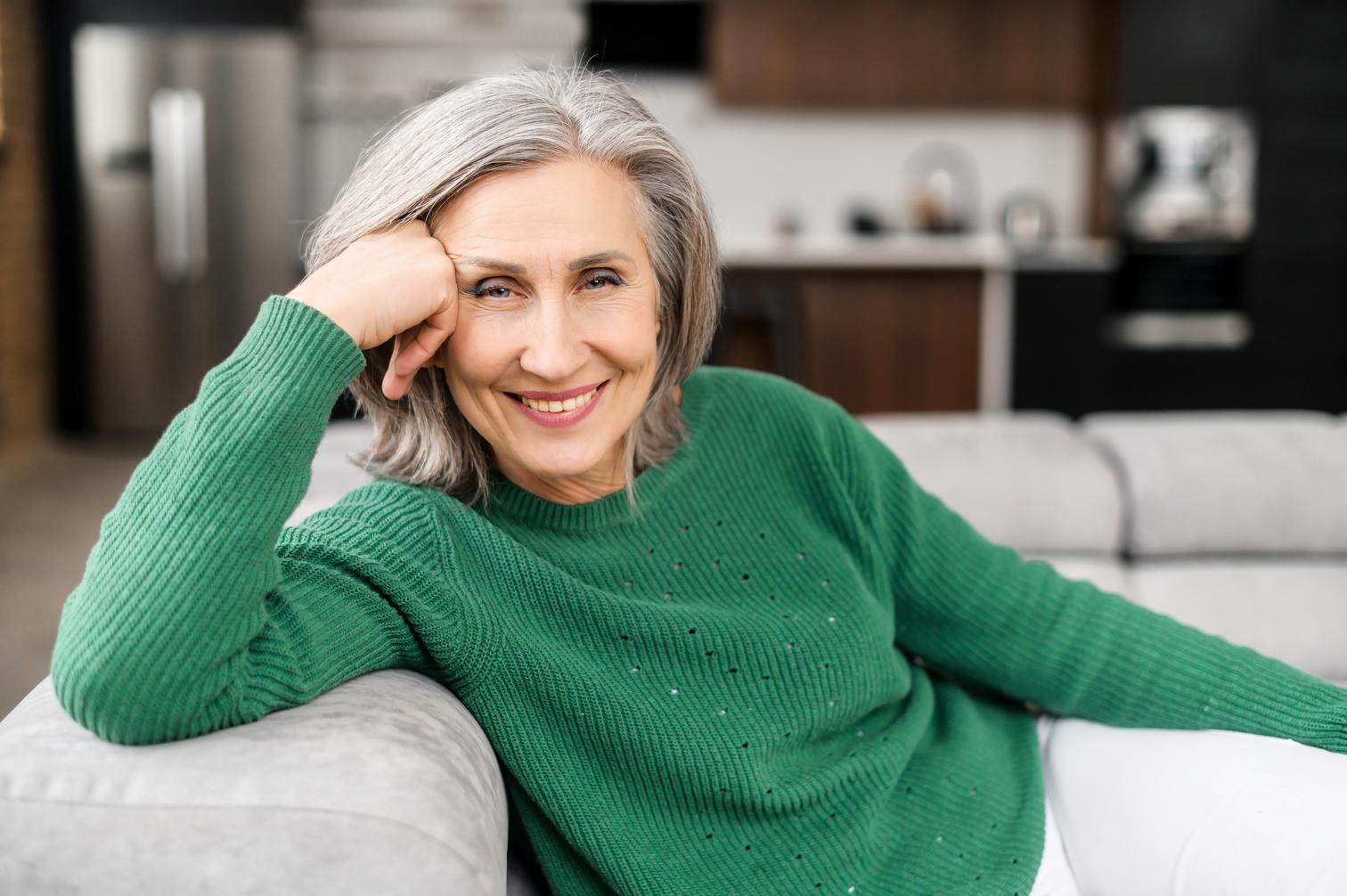 Ältere Dame im grünen Pullover sitzt auf dem Sofa und lächelt in die Kamera